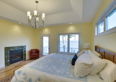 master bedroom with fireplace, bed, and water view