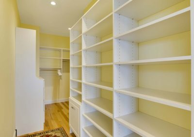 walk in closet with open white shelving