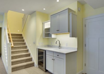 wet bar in basement of home with stairs to the left