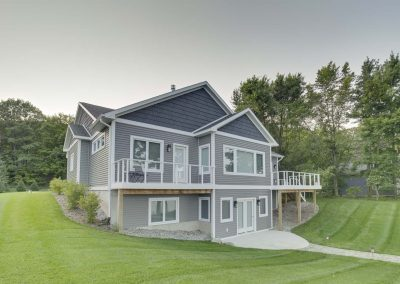 large gray home with white trim and large backyard